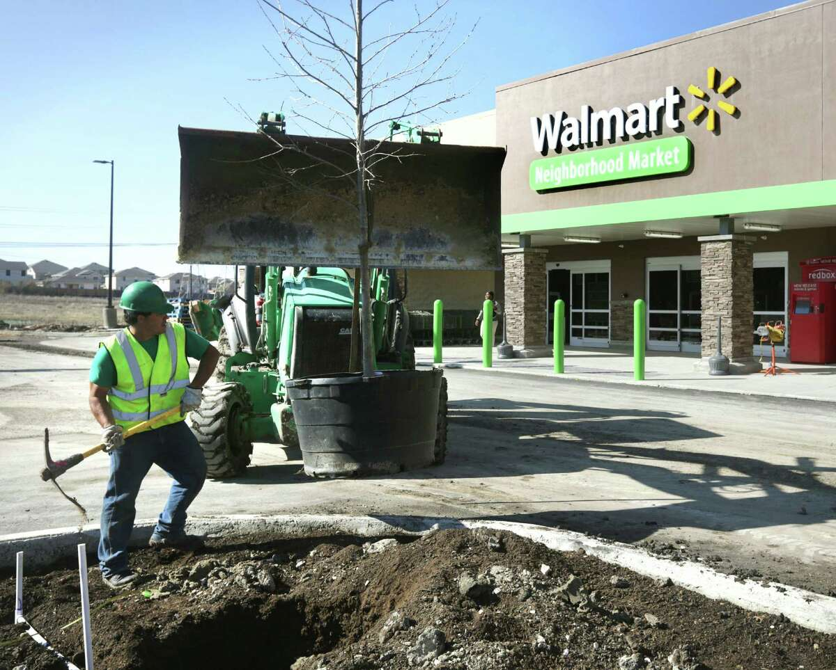A worker plants a tree Feb. 27 at the new Walmart Neighborhood Market at Ellison Drive and Marbach Road. Another is planned on DeZavala Road.