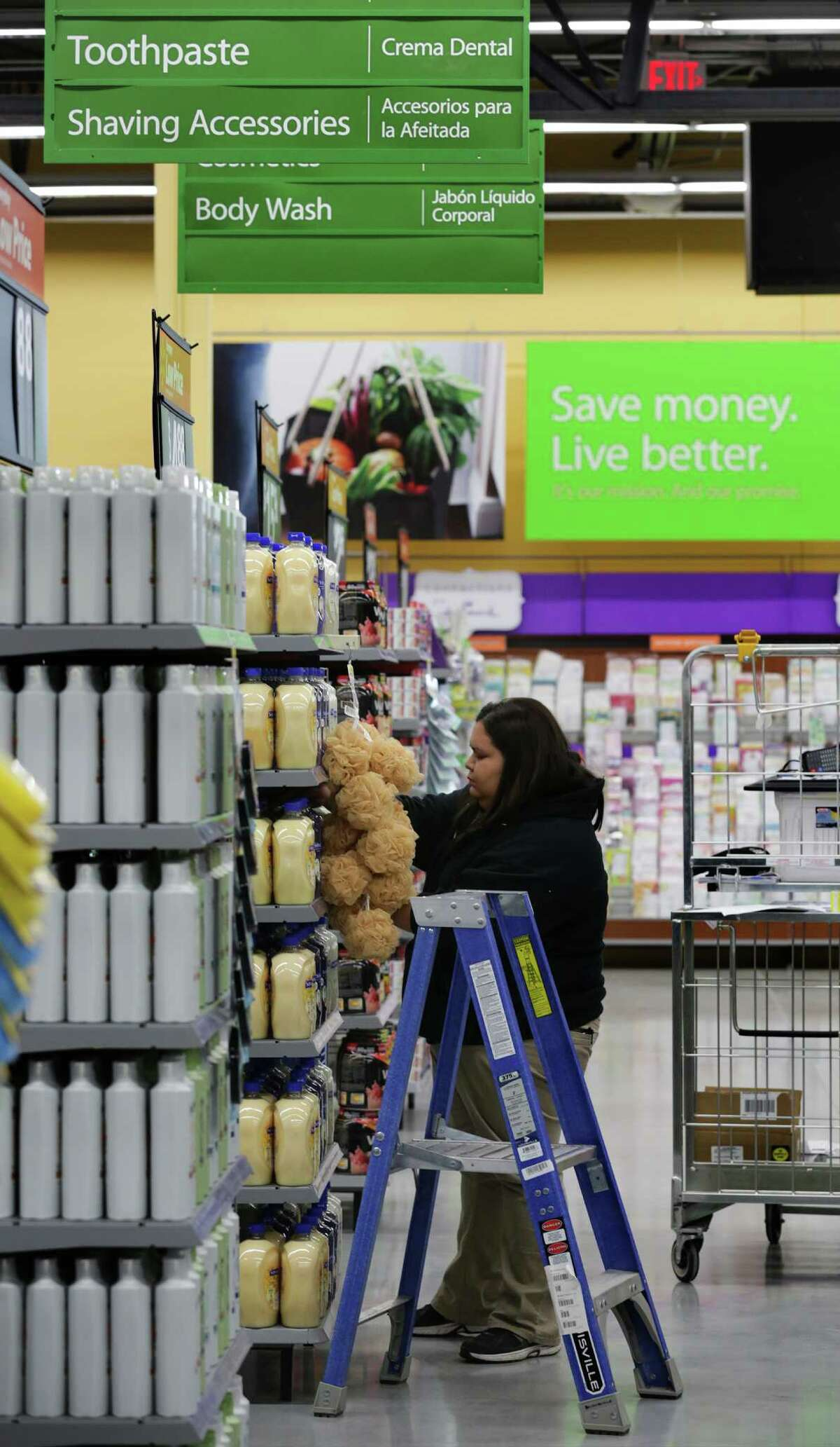 Marcie Terrazas, a cashier at the new Walmart Market, adjusts items on a shelf. Walmart will be opening it's first Neighborhood Market store in San Antonio at the corners of Ellison Dr. and Marbach Rd., which will focus on grocery, pharmacy and some general merchandise items. Thursday, Feb. 27, 2014.