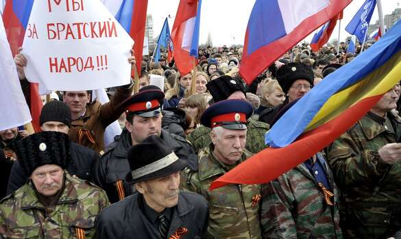 """People wearing cossack's hats take part in a rally in the southern city of Rostov-on-Don, on March 4, 2014, in support of ethnic Russians in the Crimea and Eastern Ukraine. The paster reads: """"We support the brother people!""""  President Vladimir Putin, who recently won approval from Russia's upper house of parliament to send troops into Ukraine due to the stand-off in Crimea, said today there was currently no need for military action -- but Moscow reserved the right to do so. AFP PHOTO / ANDREY KRONBERGANDREY KRONBERG/AFP/Getty Images Photo: ANDREY KRONBERG, AFP/Getty Images"""