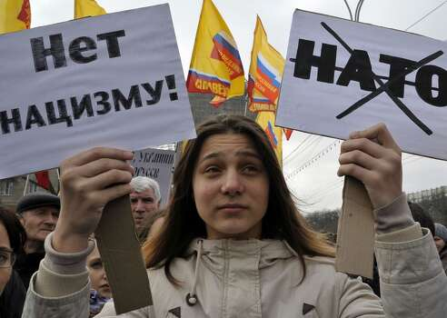 """A young woman takes part in a rally in the southern city of Rostov-on-Don, on March 4, 2014, in support of ethnic Russians in the Crimea and Eastern Ukraine. The posters read: """"No to Nazism!"""" (L), a Russian crossed-out acronym for NATO (R). President Vladimir Putin, who recently won approval from Russia's upper house of parliament to send troops into Ukraine due to the stand-off in Crimea, said today there was currently no need for military action -- but Moscow reserved the right to do so. AFP PHOTO / ANDREY KRONBERGANDREY KRONBERG/AFP/Getty Images Photo: ANDREY KRONBERG, AFP/Getty Images"""