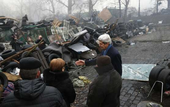 """US Secretary of State John Kerry (second on the right) stands beside a barricade at the Shrine of the Fallen in Kiev on March 4, 2014. The Shrine of the Fallen, located on Institutska Street, honors the fallen """"Heroes"""" of the """"Heavenly Sotnya"""" (Hundred). Over the course of the EuroMaidan protests, almost 100 protesters were killed by police. Most of them died on February 20 killed by sniper or automatic weapons fire on Institutska Street.  US Secretary of State John Kerry arrived in Kiev Tuesday for talks with Ukraine's new interim government, amid an escalating crisis in Crimea. His visit came as the United States said it would provide $1 billion to financially-stricken Ukraine as part of an international loan.  With the Black Sea peninsula of Crimea under near complete control by pro-Russian forces, US officials said Moscow could face sanctions within days. AFP PHOTO / POOL - Kevin LamarqueKEVIN LAMARQUE/AFP/Getty Images Photo: KEVIN LAMARQUE, AFP/Getty Images"""