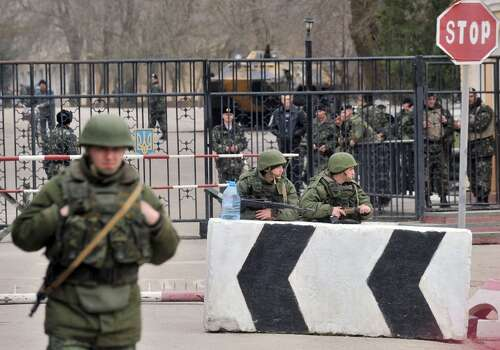 Members of the Russian forces stand guard at the gateway of Ukrainian unit in the small Crimean city of Kerch 4, 2014.The Russian Black Sea Fleet commander Aleksandr Vitko has issued an ultimatum to the Ukrainian military personnel in Crimea, the Interfax-Ukraine news agency reported. Ukraine accused Russia on March 3 of pouring more troops into Crimea as world leaders grappled with Europe's worst standoff since the Cold War and the Moscow market plunged on fears of an all-out conflict. AFP PHOTO/ GENYA SAVILOVGENYA SAVILOV/AFP/Getty Images Photo: GENYA SAVILOV, AFP/Getty Images