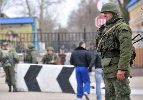 Members of the Russian forces stand guard at the gateway of Ukrainian unit in the small Crimean city of Kerch 4, 2014.The Russian Black Sea Fleet commander Aleksandr Vitko has issued an ultimatum to the Ukrainian military personnel in Crimea, the Interfax-Ukraine news agency reported. Ukraine accused Russia on March 3 of pouring more troops into Crimea as world leaders grappled with Europe's worst standoff since the Cold War and the Moscow market plunged on fears of an all-out conflict. AFP PHOTO AFP PHOTO/ GENYA SAVILOVGENYA SAVILOV/AFP/Getty Images Photo: GENYA SAVILOV, AFP/Getty Images