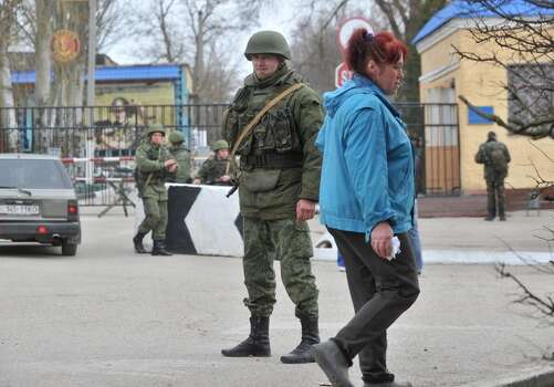 A woman walks past members of the Russian forces standing guard at the gateway of Ukrainian unit in the small Crimean city of Kerch 4, 2014.The Russian Black Sea Fleet commander Aleksandr Vitko has issued an ultimatum to the Ukrainian military personnel in Crimea, the Interfax-Ukraine news agency reported. Ukraine accused Russia on March 3 of pouring more troops into Crimea as world leaders grappled with Europe's worst standoff since the Cold War and the Moscow market plunged on fears of an all-out conflict. AFP PHOTO/ GENYA SAVILOVGENYA SAVILOV/AFP/Getty Images Photo: GENYA SAVILOV, AFP/Getty Images