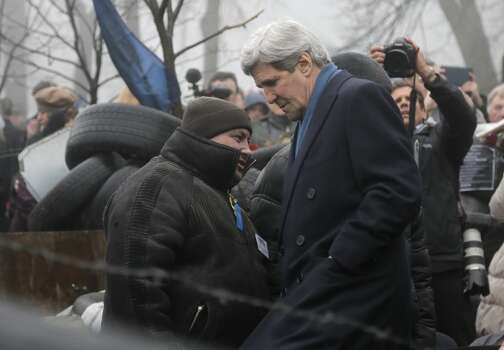 U.S. Secretary of State John Kerry, right, inspects protesters barricades in Kiev, Ukraine, Tuesday, March, 4, 2014. In a somber show of U.S. support for Ukraine's new leadership, Secretary of State John Kerry walked the streets Tuesday where nearly 100 anti-government protesters were gunned down by police last month, and promised beseeching crowds that American aid is on the way.  The Obama administration announced a $1 billion energy subsidy package in Washington as Kerry was arriving in Kiev.(AP Photo/Efrem Lukatsky) Photo: Efrem Lukatsky, Associated Press