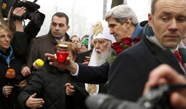 """Secretary of State John Kerry talks with a religious leader as views the Shrine of the Fallen in Kiev, Ukraine, Tuesday, March 4, 2014. The Shrine of the Fallen, located on Institutska Street, honors the fallen Heroes of the """"Heavenly Sotnya"""" (Hundred). Over the course of the EuroMaidan protests, almost 100 protesters were killed by police. (AP Photo/Kevin Lamarque, Pool) Photo: Kevin Lamarque, Associated Press"""