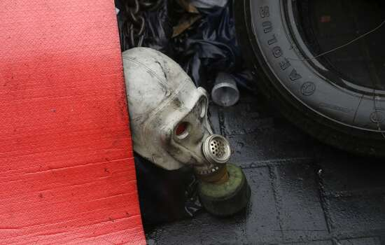 """A gas mask lies among other debris at a barricade where Secretary of State John Kerry was visiting, Tuesday, March 4, 2014, at the Shrine of the Fallen in Kiev, Ukraine. The Shrine of the Fallen, located on Institutska Street, honors the fallen Heroes of the """"Heavenly Sotnya"""" (Hundred). Over the course of the EuroMaidan protests, almost 100 protesters were killed by police. (AP Photo/Kevin Lamarque, Pool) Photo: Kevin Lamarque, Associated Press"""