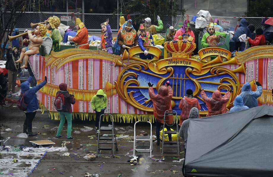 Members of the Krewe of Rex, throw beads and trinkets from a float along a largely empty St. Charles Ave., during Mardi Gras in New Orleans, Tuesday, March 4, 2014. Rain and cold temperatures kept the normally massive and festive crowds away. (AP Photo/Gerald Herbert) Photo: Gerald Herbert, Associated Press