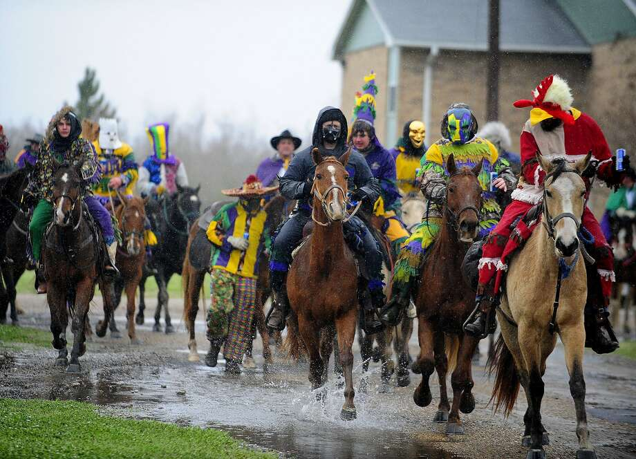 Costumed runners ride in the Courir de Mardi Gras à Grand Mamou in Mamou, La., Tuesday, March 4, 2014. Participants continue the tradition of chasing chickens and traveling to local homes to gather ingredients for a community gumbo.  Photo: Paul Kieu, Associated Press