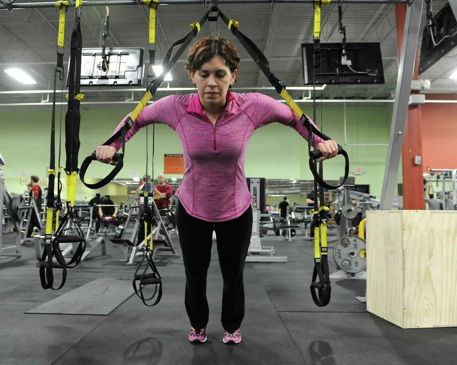 Lisa Belrose of Rotterdam does a push-up exercise on the TRX as she works out at Best Fitness on Wednesday, Feb. 19, 2014 in Schenectady, N.Y.  (Lori Van Buren / Times Union) Photo: Lori Van Buren / 00025782A