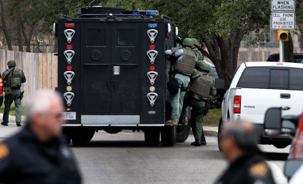 San Antonio police work at the scene of a standoff Tuesday March 4, 2014 on the 800 block of Silver Spruce near Hidden Forest Elementary School. San Antonio police sergeant Javier Salazar said police received a call near the noon hour about a distraught woman in a house near the school and that police persuaded her to come out of the house. The school was placed on lockdown as a precaution, and nobody was injured.