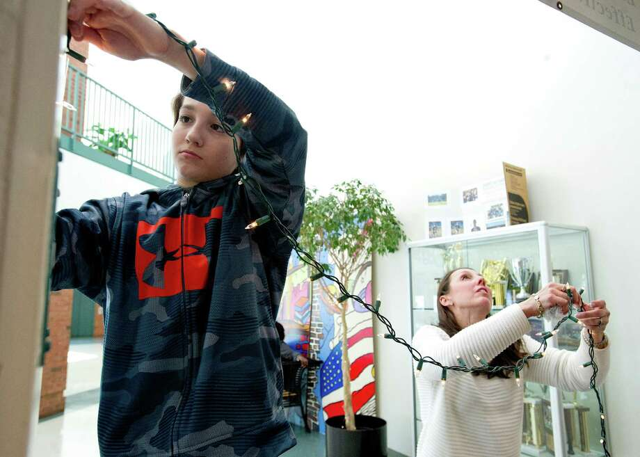 Ian Lawler, 12, and his mother, Jessica, help decorate at Scofield Magnet School for the dance on Friday, February 28, 2014. Photo: Lindsay Perry / Stamford Advocate