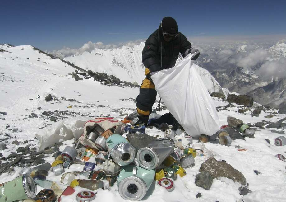 A Sherpa collects garbage at 26,000 feet. Under new rules, Mount Everest climbers will have to bring back 17.6 pounds of trash. Photo: Namgyal Sherpa, AFP/Getty Images