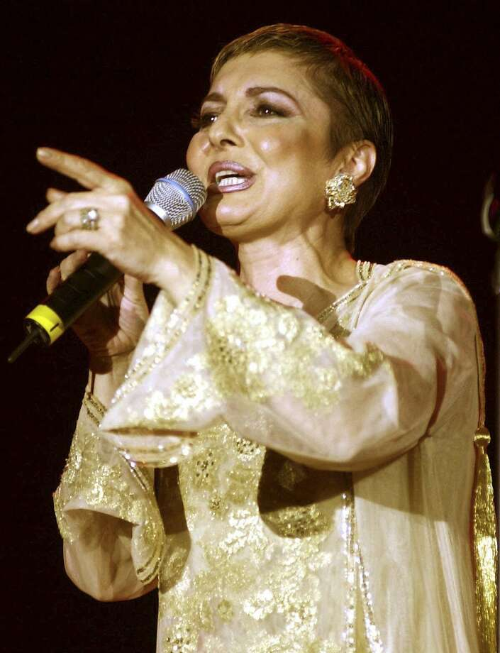 "FILE - In this March 21, 2001 file photo Iranian pop star Googoosh performs during a concert in Dubai, United Arab Emirates. Googoosh has released a video that addresses homosexual love, a major gesture by one of the country's top cultural figures in exile, causing shockwaves in the Islamic republic. Googoosh sings ""don't tell me to stop loving: you can't do that and I can't either."" Googoosh was Iran's first pop diva, though the 1979 revolution ended her live singing career for two decades until she immigrated to the West. Navid Akhavan, an Iranian-born German who wrote and directed the video for Googoosh's song ?Behesht? (Heaven), said it has been viewed by more than a million Iranians online or via illegal satellite channels since its Valentine's Day release. (AP Photo/Kamran Jebreili, File) Photo: Kamran Jebreili, Associated Press"