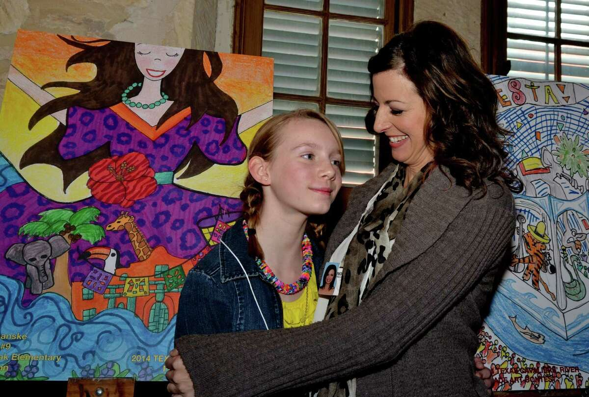 Rose Ganske, left, a student at Stone Oak Elementary School, gets a hug from the school's art teacher Charisse Dennis as they stand by the artwork Rose produced. That drawing was named the grand prize winner of this year's Texas Cavaliers River Parade art contest.