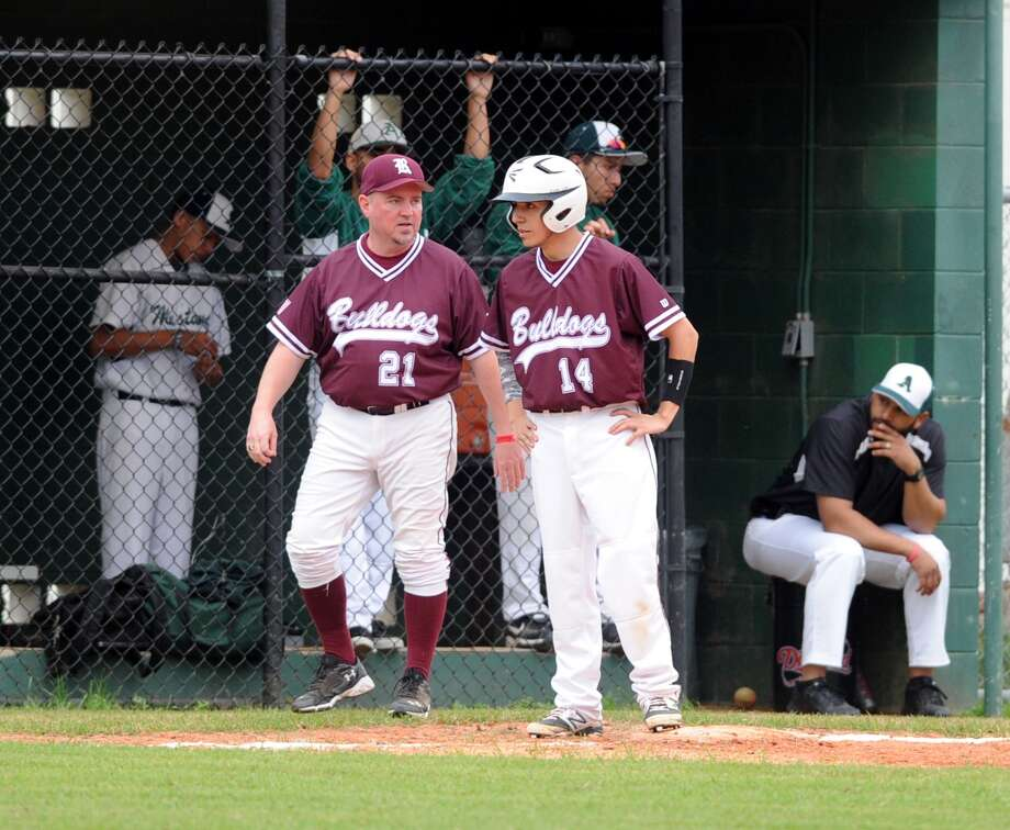 Reagan Baseball team plays in UIL District 21-4A. Left, Coach David Petty gives instructions to base runner Christian Cobian (14). Photo: Eddy Matchette, Freelance / Freelance