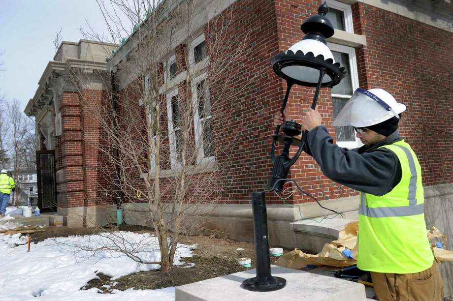 Electrician Stephen Heise installs one of two outside lanterns at the Ridgefield Library which is undergoing major renovations, Tuesday, March 4, 2014. Photo: Carol Kaliff / The News-Times