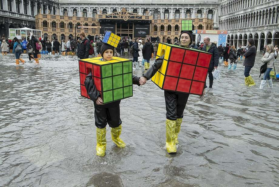 Puzzling costumes:High water in Venice's St. Mark's Square can't keep mother-and-son Rubik's Cubes away. Photo: Marco Secchi, Getty Images