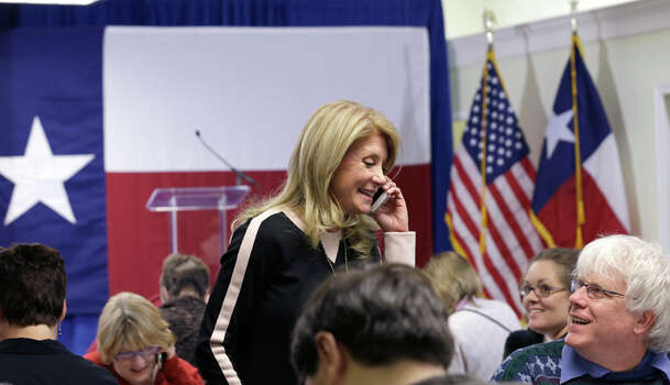 Texas Sen. Wendy Davis, D-Fort Worth, left, speaks on a phone given to her by volunteer Daniel O'Leary, right, during a visit to her campaign headquarters, Tuesday, March 4, 2014, in Fort Worth, Texas. Texas is holding the nation's first primary election Tuesday with a political free-for-all in Republican races that could push the state further right, though Democrats are calling it the next big electoral battleground with Davis running for governor.  (AP Photo/LM Otero) Photo: LM Otero, Associated Press / AP