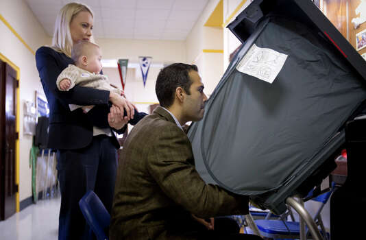 George P. Bush, with his wife Amanda and son Prescott, prepares to vote in the primary election  Tuesday, March 4, 2014, at North High Mount Elementary School in Fort Worth, Texas. The 37-year-old nephew of former President George W. Bush, and son of former Florida Gov. Jeb Bush, is running for land commissioner in the state. (AP Photo/The Fort Worth Star-Telegram, Joyce Marshall) Photo: Joyce Marshall, Associated Press / The Fort Worth Star-Telegram