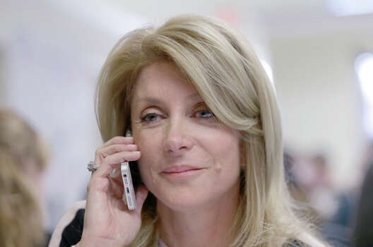 Texas Sen. Wendy Davis, D-Fort Worth, left, makes a phone call to a potential voter during a visit  to  her campaign headquarters Tuesday, March 4, 2014, in Fort Worth, Texas. Texas is holding the nation's first primary election Tuesday with a political free-for-all in Republican races that could push the state further right, though Democrats are calling it the next big electoral battleground with Davis running for governor.  (AP Photo/LM Otero) Photo: LM Otero, Associated Press / AP