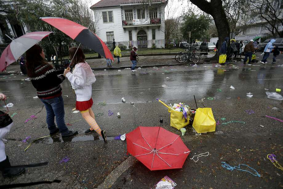 Umbrellas and beads lie in the street during Mardi Gras day in New Orleans, Tuesday, March 4, 2014. Rain and unusually cold temperatures kept much of the normally massive and festive crowds away. (AP Photo/Gerald Herbert) Photo: Gerald Herbert, Associated Press