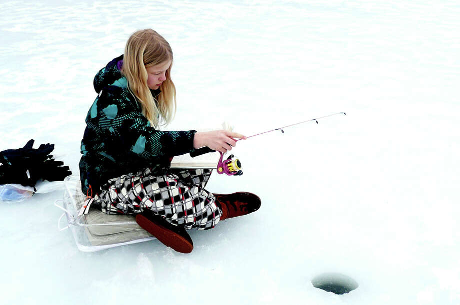 """Sophie Anderlind catches up on her reading while ice fishing on the Mianus River in Greenwich, Conn. """"This is the best ever,"""" says mother Samantha Anderlind. """"No video games, reading and fishing, complete relaxation, complete serenity."""" Photo: Anne W. Semmes / Greenwich Time"""