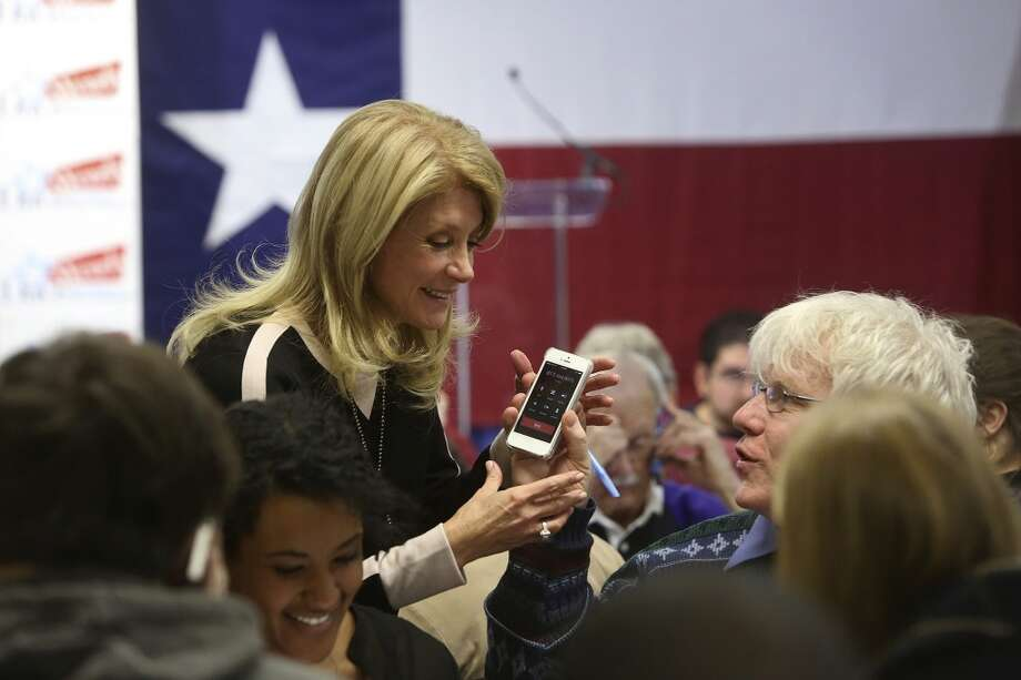 Volunteer Daniel O'Leary hands Senator Wendy Davis his phone so she can talk to a voter he called as she calls voters and thanks volunteers working at the phone bank at her campaign headquarters in Fort Worth on Tuesday, March 4, 2014. Photo: Lisa Krantz, San Antonio Express-News