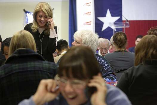 Senator Wendy Davis talks to a voter who volunteer Daniel O'Leary, right, called as she calls voters and thanks volunteers working at the phone bank at her campaign headquarters in Fort Worth on Tuesday, March 4, 2014. Photo: Lisa Krantz, San Antonio Express-News