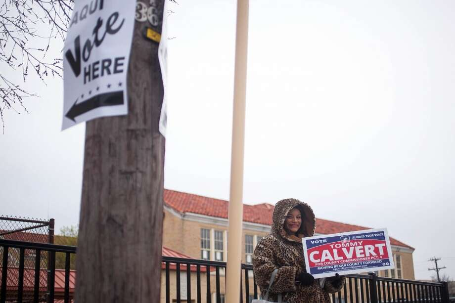 Volunteer Joy McGhee holds up a sign while directing voters to the polls Tuesday March 4, 2014 at Travis Early College High School of off 1915 N. Main Ave. McGhee said the weather probably discouraged more voters to come out early this morning. Photo: Julysa Sosa, For The San Antonio Express-News