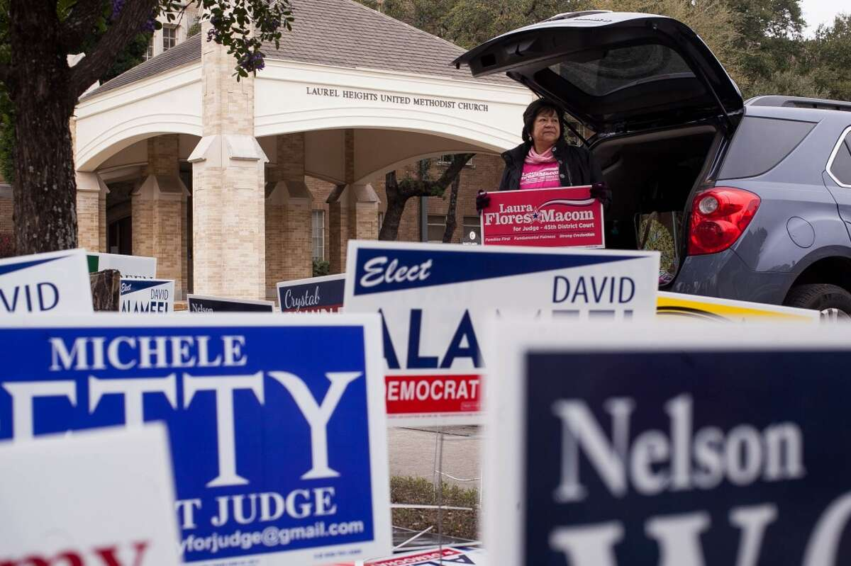 Volunteer Mary Helen Santillan holds up a sign while directing voters to the polls Tuesday March 4, 2014 in front of Laurel Heights United Methodist Church at 227 W Woodlawn Ave. Voting polls are open until 7 p.m. tonight.