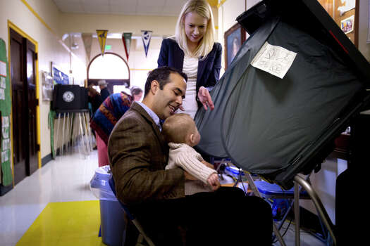 George P. Bush, holding his son Prescott with his wife Amanda, prepares to vote in the primary election  Tuesday, March 4, 2014, at North High Mount Elementary School in Fort Worth, Texas. The 37-year-old nephew of former President George W. Bush, and son of former Florida Gov. Jeb Bush, is running for land commissioner in the state. Photo: Joyce Marshall, AP Photo/The Fort Worth Star-Telegram / The Fort Worth Star-Telegram