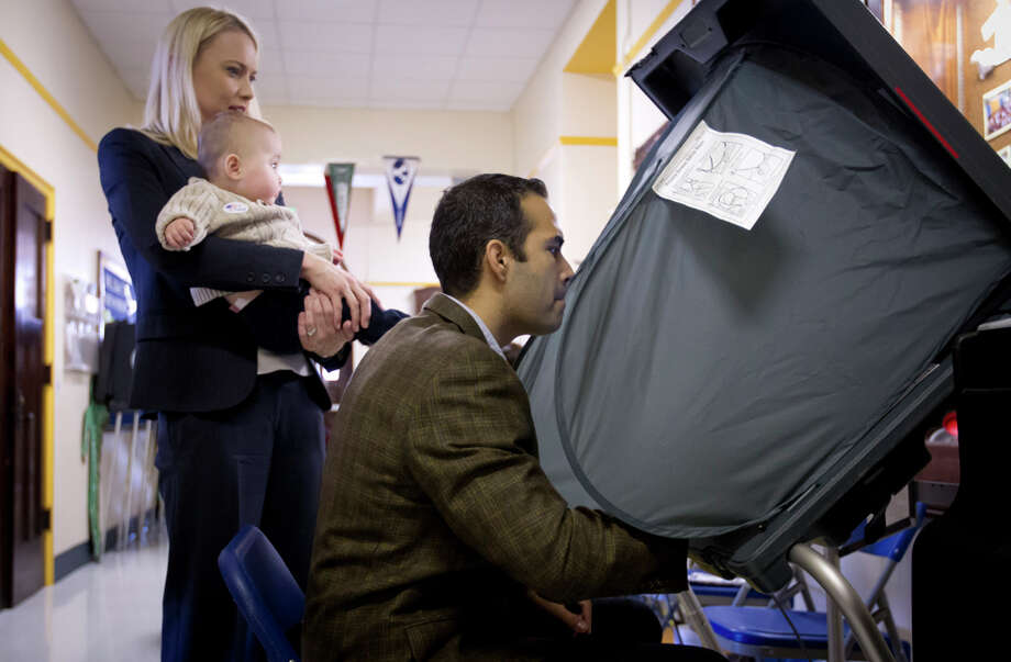 George P. Bush, with his wife Amanda and son Prescott, prepares to vote in the primary election  Tuesday, March 4, 2014, at North High Mount Elementary School in Fort Worth, Texas. The 37-year-old nephew of former President George W. Bush, and son of former Florida Gov. Jeb Bush, is running for land commissioner in the state. Photo: Joyce Marshall, AP Photo/The Fort Worth Star-Telegram / The Fort Worth Star-Telegram