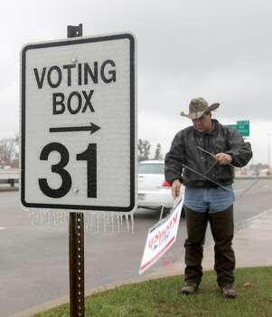 A political supporter adjusts a campaign sign in front of the Shenandoah Municipal Complex Tuesday, March 4, 2014, in Shenandoah. Texas. A blast of winter weather hit the region Monday sending windchill temperatures into the 20s and leaving residents with icy conditions on the road for Texas' primary elections on Tuesday. Photo: Jason Fochtman, AP Photo/Conroe Courier