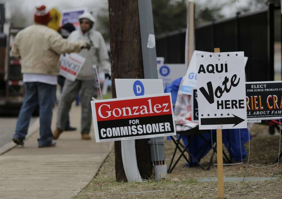 Campaign volunteers hold signs outside of a polling site, Tuesday, March 4, 2014, in San Antonio. Texas is holding the nation's first primary election Tuesday with a political free-for-all in Republican races that could push the state further right, though Democrats are calling it the next big battleground on the electoral map. Photo: Eric Gay, Associated Press