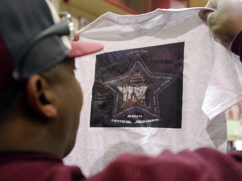 Michael Jacquet looks at a team shirt printed for the Central High School Jaguars boys basketball team Tuesday. The Central Medical Magnet High School boys basketball team was given a strong send-off by friends and family as they left Tuesday afternoon for the state championships in Austin. Central will play against Kimball High School on Thursday. Photo taken Tuesday, 3/4/14 Jake Daniels/@JakeD_in_SETX Photo: Jake Daniels / ©2014 The Beaumont Enterprise/Jake Daniels