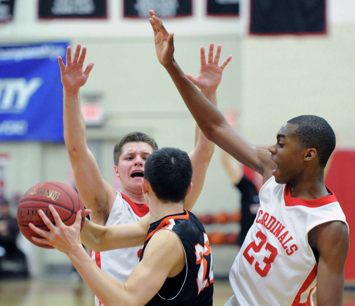 Greenwich defenders, Tommy Povinelli, left, and Leonel Hyatt, right, block the passing avenue of Ridgefield's Zachary Ward (# 22) during the FCIAC boys basketball semfinal game between Greenwich High School vs. Ridgefield High School at Fairfield Warde High School, Fairfield, Conn., Tuesday, March 4, 2014. Greenwich defeated Ridgefield, 65-54, and advances to the final that will be played at Fairfield Warde High School Thursday, March 6, at 7 p.m.