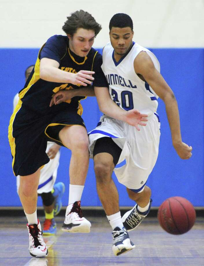 Weston's Grant Limone, left, and Bunnell's Aaron Woods battle for possession in No. 2 Bunnell's 46-45 overtime win over No. 3 Weston in the SWC boys basketball semifinal game at Newtown High School in Newtown, Conn. Tuesday, March 4, 2014. Photo: Tyler Sizemore / The News-Times