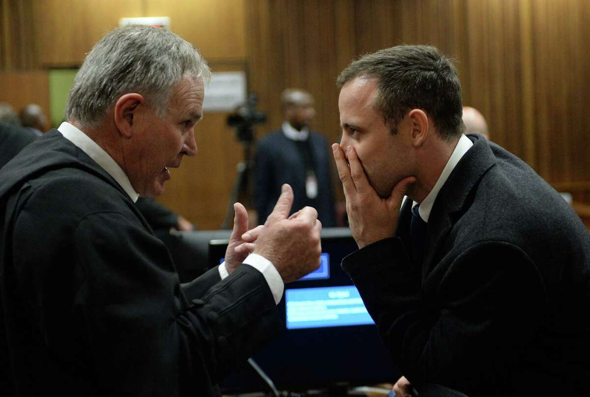 Oscar Pistorius (right), speaking with chief defense lawyer Barry Roux, faces at least 25 years in prison if he is convicted.