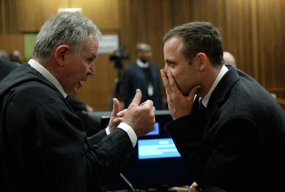 Oscar Pistorius (right), speaking with chief defense lawyer Barry Roux, faces at least 25 years in prison if he is convicted. Photo: Antoine De Ras / Getty Images / AFP