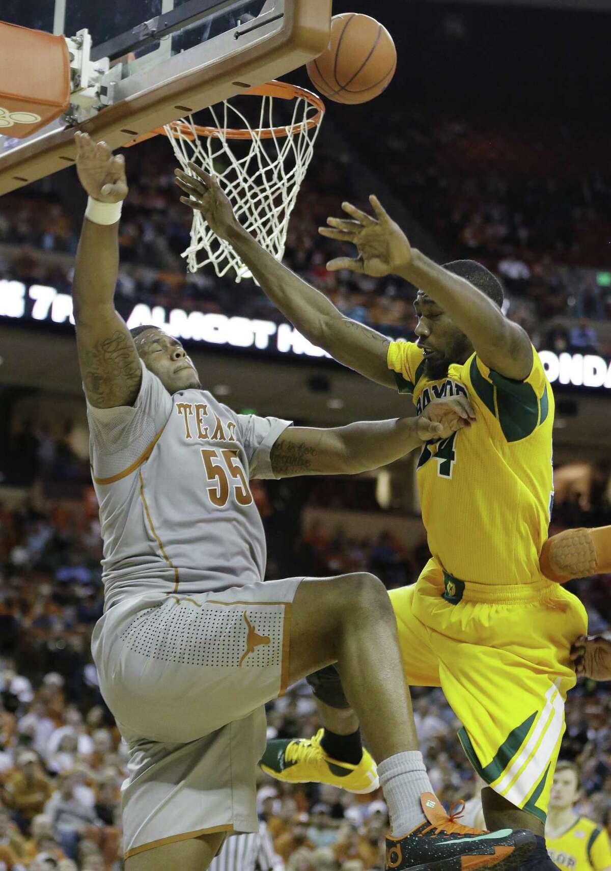Texas' Cameron Ridley (55) blocks Baylor's Cory Jefferson (34) during the second half of an NCAA college basketball game, Wednesday, Feb. 26, 2014, in Austin, Texas. Texas won 74-69. (AP Photo/Eric Gay)