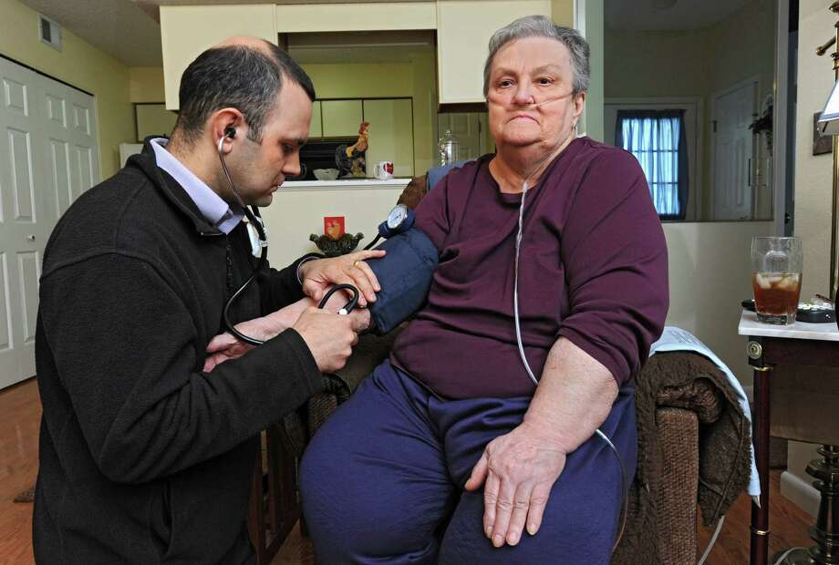 Dr. Christopher Domarew takes the blood pressure of 75 year-old patient Leona Mantellow during a house call as part of a new program on Monday, March 3, 2014 in North Greenbush, N.Y. (Lori Van Buren / Times Union) Photo: Lori Van Buren / 00025972A