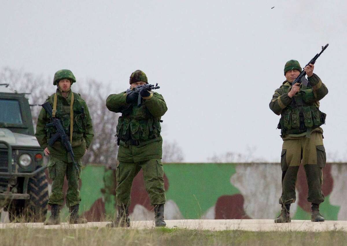 Russian soldiers fire warning shots at the Belbek air base, outside Sevastopol, Ukraine, on Tuesday, March 4, 2014. Russian troops, who had taken control over Belbek airbase, fired warning shots in the air as around 300 Ukrainian officers marched towards them to demand their jobs back. (AP Photo/Ivan Sekretarev) ORG XMIT: XIAS102