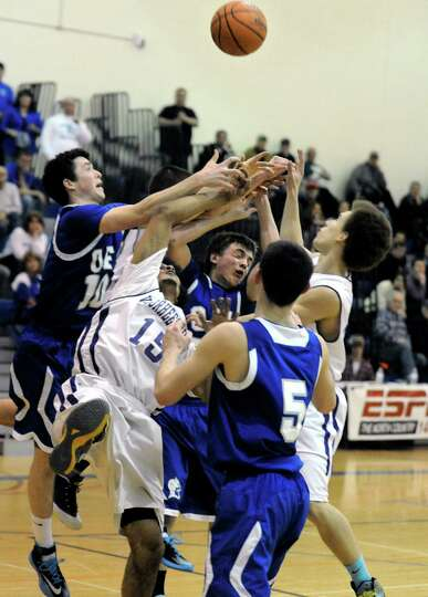 Voorheesville and Ogdensburg Free Academy players battle for a rebound during their Class B state re