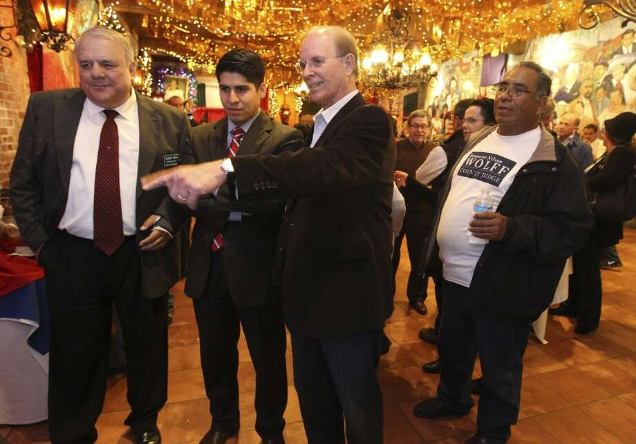 Bexar County Judge Nelson Wolff (center) monitors election night results with supporters including Bexar County Tax Assessor-Collector Albert Uresti (left) and District 4 City Councilman Rey Saldana (second from left) at Mi Tierra on Tuesday, Mar. 4, 2014. Wolff ran against Bexar County Commissioner Tommy Adkisson. (Kin Man Hui/San Antonio Express-News) Photo: Kin Man Hui, San Antonio Express-News