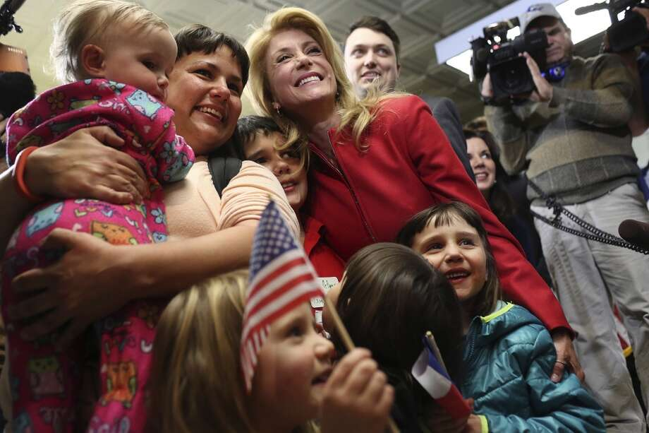 State Senator and Democratic gubernatorial candidate Wendy Davis poses with Jessica Womack, holding her daughter, Sarah Womack, 1, and her other children, Sam Peters, 12, and daughters, from left, Emma Joan Peters, 3, Lola Peters, 4, and Abigail Peters, 6,  during the primary election watch party at her campaign headquarters in Fort Worth on Tuesday, March 4, 2014. Photo: Lisa Krantz, San Antonio Express-News