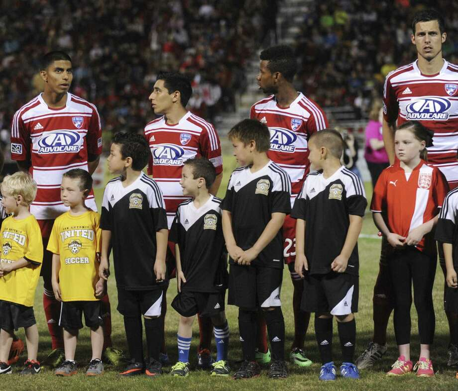 Children stand with players from FC Dallas of MLS during the Scorpions' friendly Saturday. MLS, which also has the Houston Dynamo, will likely add another team in Texas. Photo: Billy Calzada/ Express-News / San Antonio Express-News