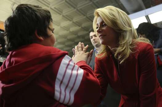 State Senator and Democratic gubernatorial candidate Wendy Davis gives a high five to supporter Sam Peters, 12, during the primary election watch party at her campaign headquarters in Fort Worth on Tuesday, March 4, 2014. Photo: SAN ANTONIO EXPRESS-NEWS