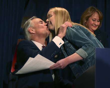 After winning the Republican nomination for Texas Governor, Texas Attorney General Greg Abbott kisses his daughter, Audrey, at Aldaco's Sunset Station, Tuesday, March 4, 2014. Abbott will face Democrat Wendy Davis in the November general elections. In back is his wife, Cecilia. Photo: San Antonio Express-News