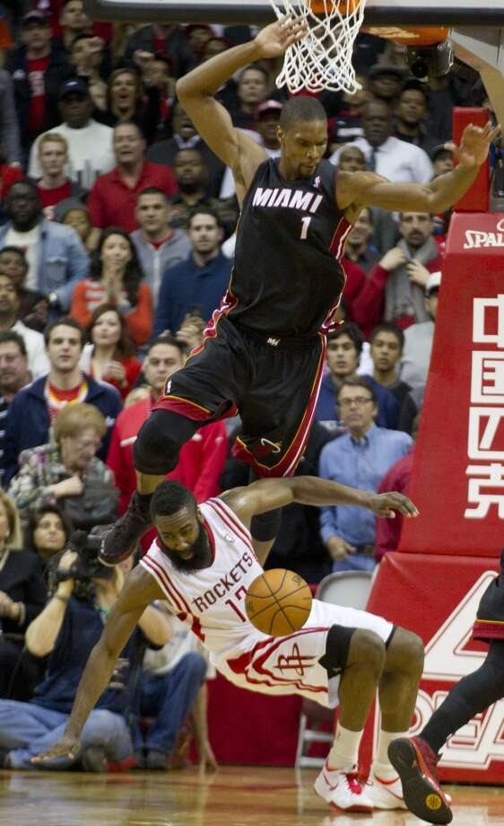 Rockets shooting guard James Harden gets tangled up with Chris Bosh of the Heat. Photo: Brett Coomer, Houston Chronicle